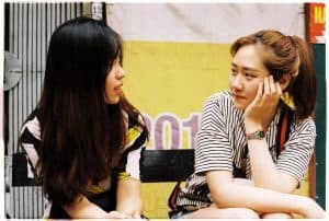 woman in white-and-black striped tops looking each other