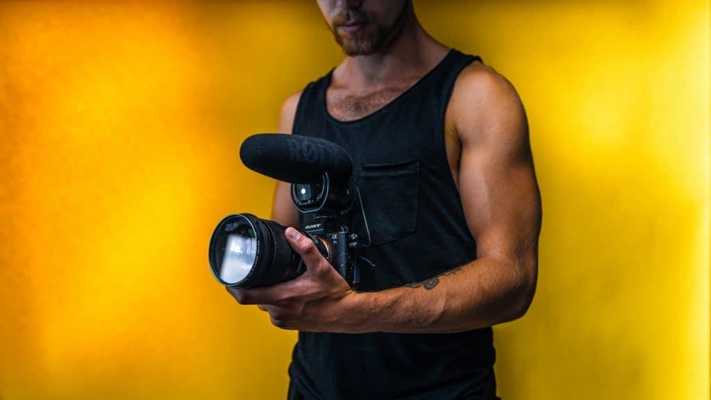 man in black tank top holding black dslr camera
