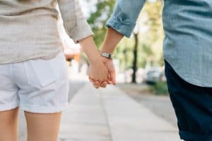 man and woman holding hands together in walkway during daytime