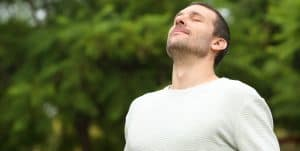 Relaxed adult man breathing fresh air in a forest